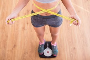 36347937 - top view of pretty slim woman with measure around her body is standing on the scales.