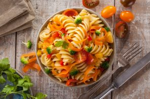 Fusilli pasta with colorful tomatoes, carrots and broccoli on a white wooden table Italian cuisine.